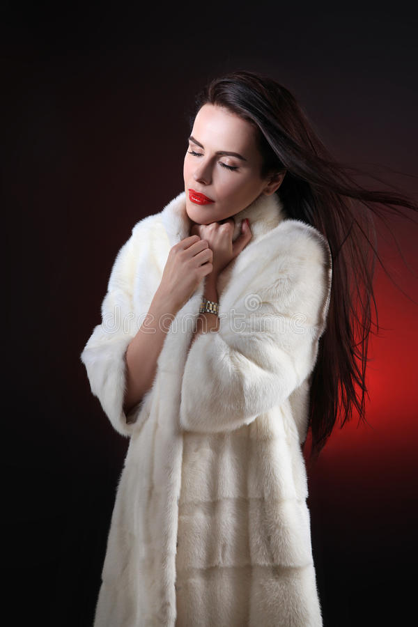 Portrait young woman with closed eyes, holding collar fur coa royalty free stock images