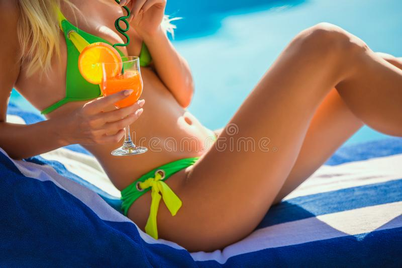 Woung woman with cocktail glass near swimming pool on a deck chair. Portrait of young woman with cocktail glass chilling in the tropical sun near swimming pool stock photos