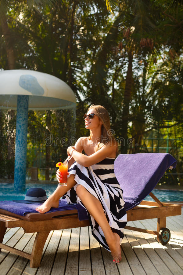 Portrait of young woman with cocktail glass near swimming pool on a deck chair with palm trees behind. Vacation concept royalty free stock photos