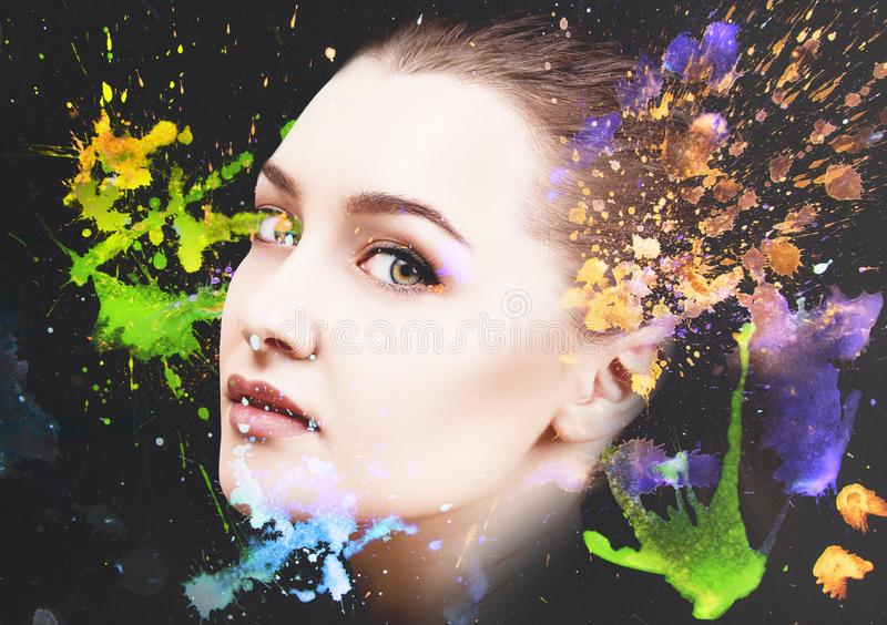Portrait of young woman and colorful paint blots. Over black background royalty free stock image