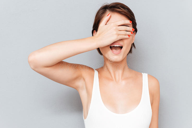 Portrait of a young woman covering her eyes with palm royalty free stock photo