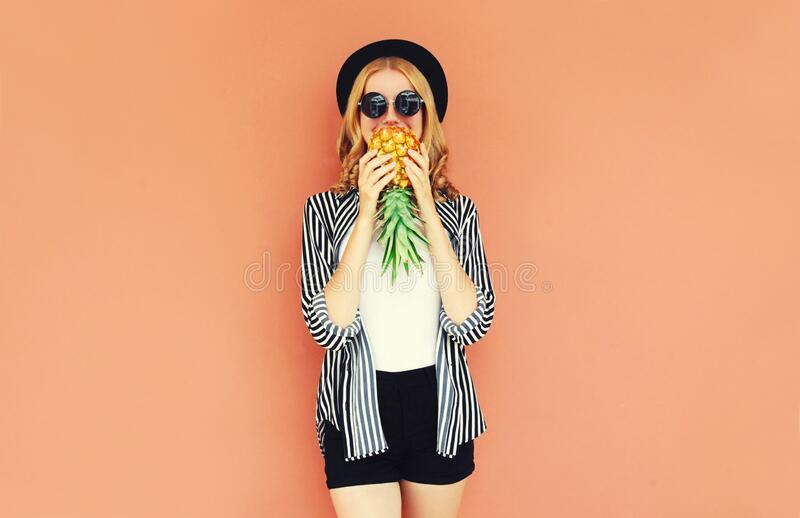 Portrait of young woman covering her mouth with pineapple wearing a black hat, sunglasses, striped shirt on background royalty free stock photography