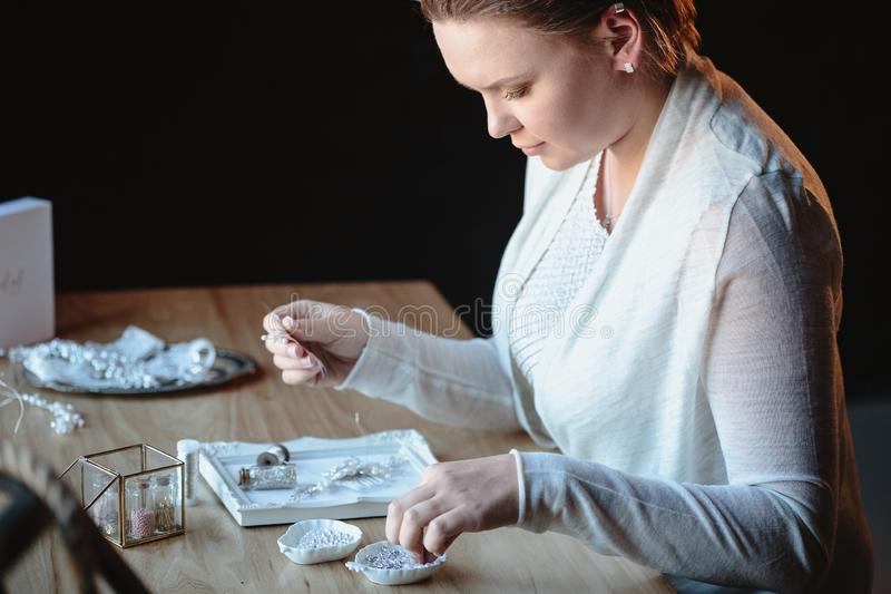 Portrait of woman, creating wedding jewelry, workplace of decorator. Woman`s hands in a process of creation royalty free stock photos