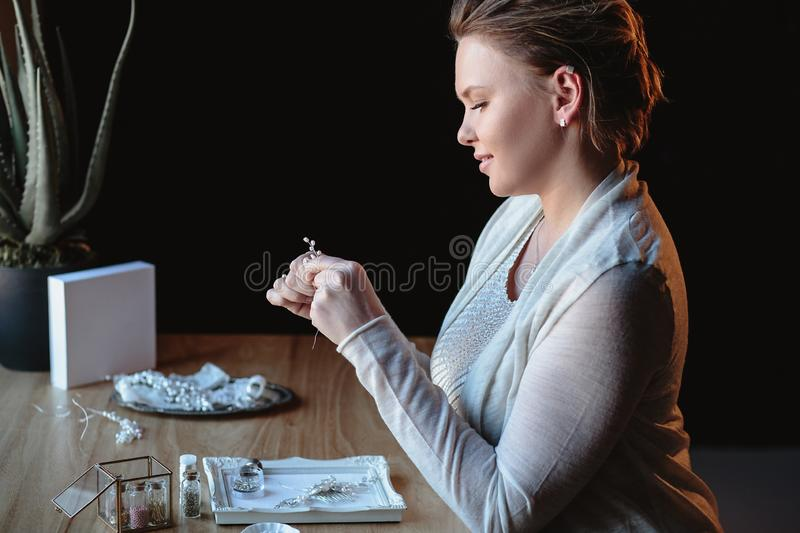 Portrait of woman, creating wedding jewelry, workplace of decorator. Woman`s hands in a process of creation stock images