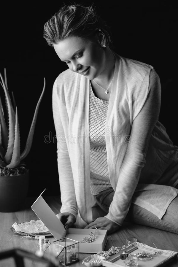 Portrait of woman, creating wedding jewelry, workplace of decorator. Woman`s hands in a process of creation stock photo