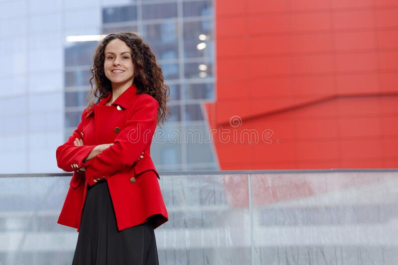 Portrait of a young woman with curly hair, with a beautiful smile, keeps her hands crossed, dressed in a red jacket. royalty free stock image
