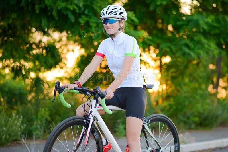 Portrait of Young Woman Cyclist Resting with Bicycle at Sunset. Sport and Healthy Lifestyle Concept. Portrait of Young Woman Cyclist Resting with Road Bicycle at royalty free stock photos