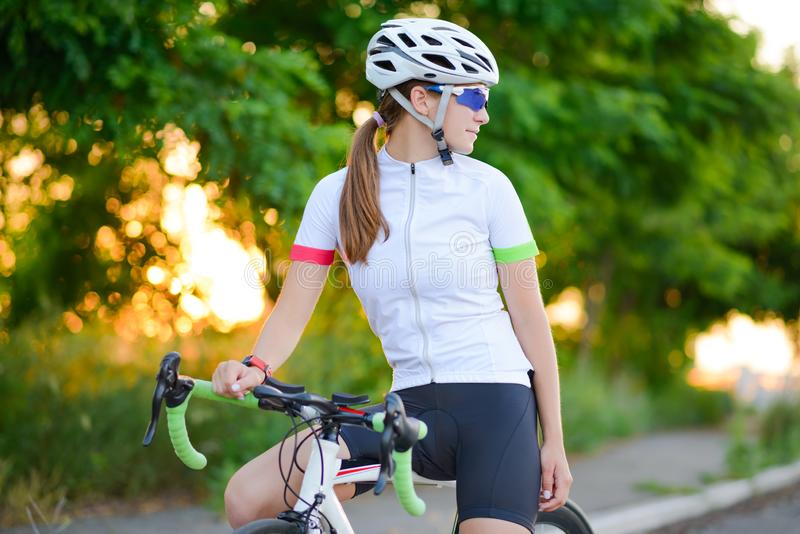 Portrait of Young Woman Cyclist Resting with Bicycle at Sunset. Sport and Healthy Lifestyle Concept. Portrait of Young Woman Cyclist Resting with Road Bicycle at stock photos