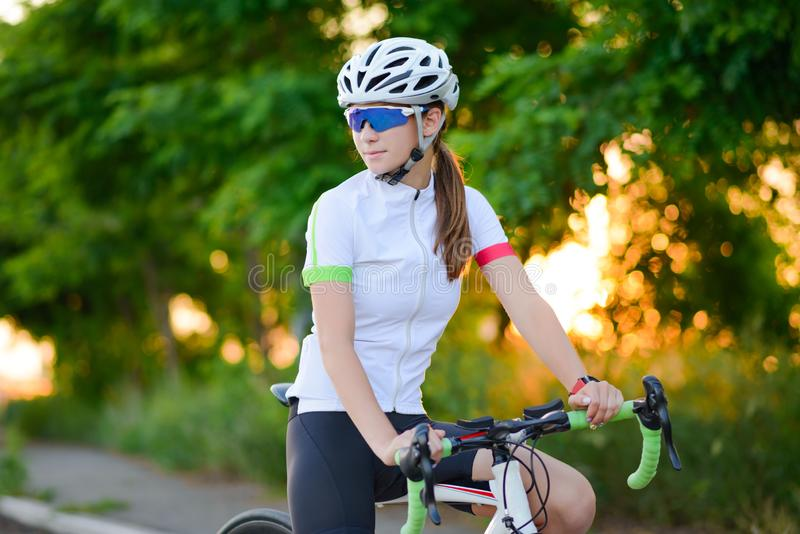 Portrait of Young Woman Cyclist Resting with Bicycle at Sunset. Sport and Healthy Lifestyle Concept. Portrait of Young Woman Cyclist Resting with Road Bicycle at royalty free stock image