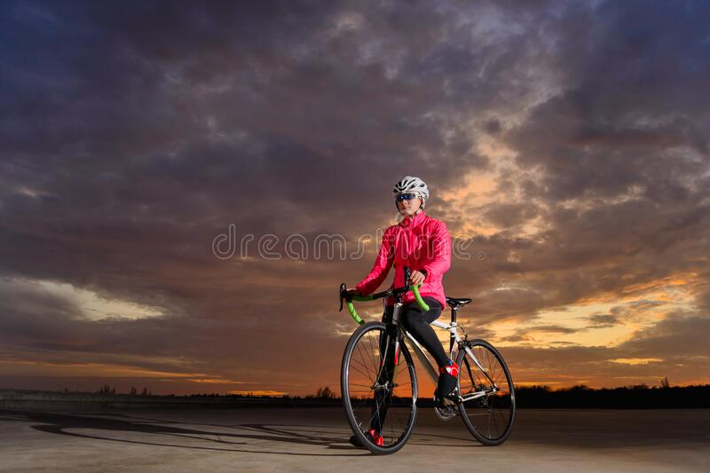 Portrait of Young Woman Cyclist with Road Bike at Sunset. Healthy Lifestyle and Outdoor Sport Concept royalty free stock images