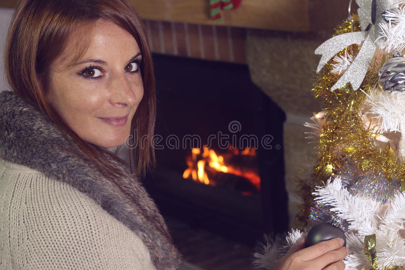 Portrait of a young woman decorating a Christmas tree. In front of a fireplace stock photo
