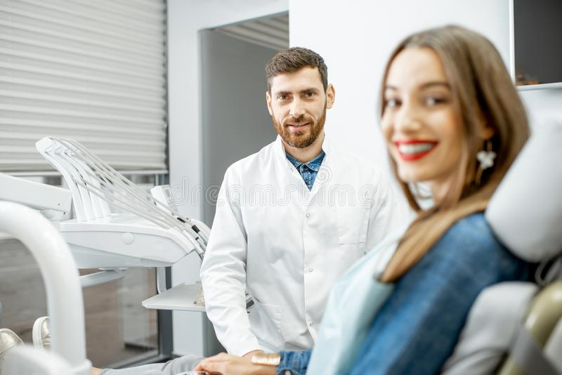 Portrait of a young woman with dentist in the dental office stock image