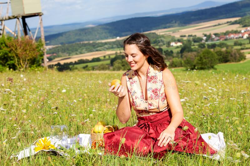 Young woman in dirndl sitting on blanket in meadow eating an apple. Portrait of young woman in dirndl sitting on blanket in meadow eating an apple stock image