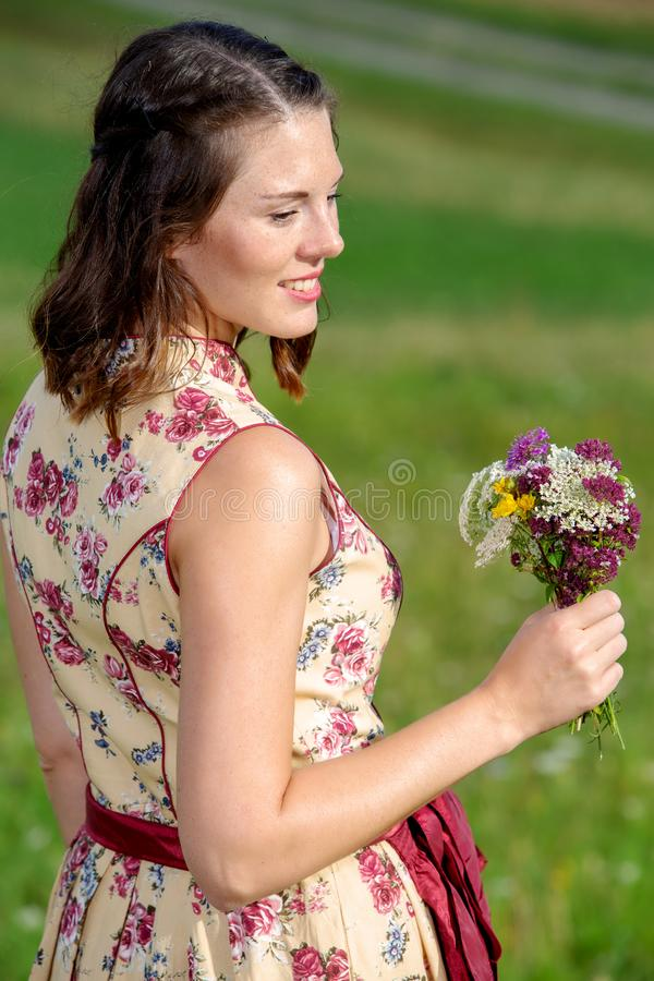 Young woman in dirndl standing outdoors and holding flowers stock image
