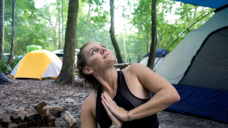 Portrait of young woman doing namaste hands praying pose and looking to the sky while doing yoga in a camping vacation royalty free stock photo