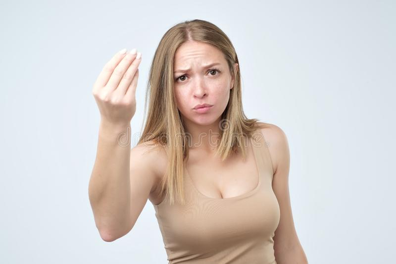 Portrait of young woman doing a typical italian gesture, frowning and looking straight ahead royalty free stock photo