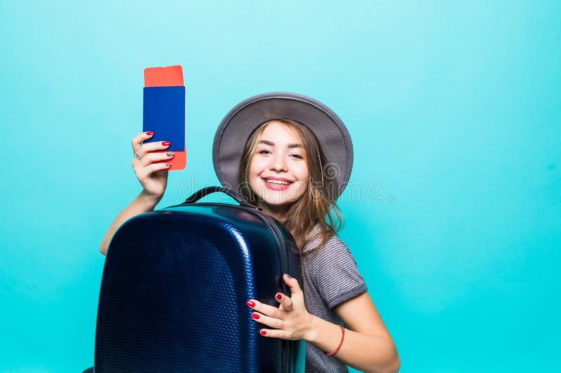 Portrait of young woman dressed in summer clothes holding passport with flying tickets standing with a suitcase over blue. Portrait of woman dressed in summer royalty free stock photos