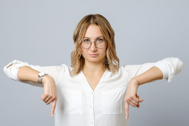 Portrait of young woman dressed in white pointing fingers down royalty free stock images