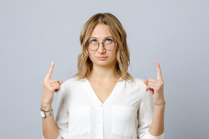 Portrait of young woman dressed in white pointing fingers up stock photos