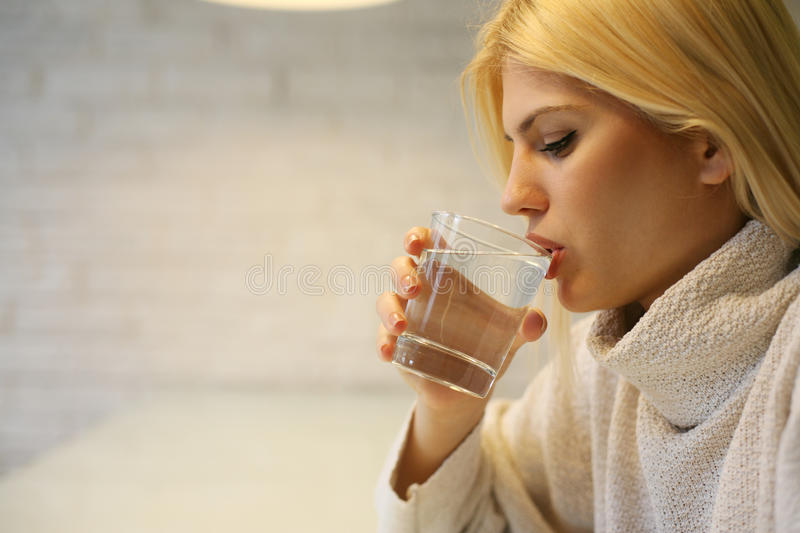 Portrait of young woman drinking water. stock photography