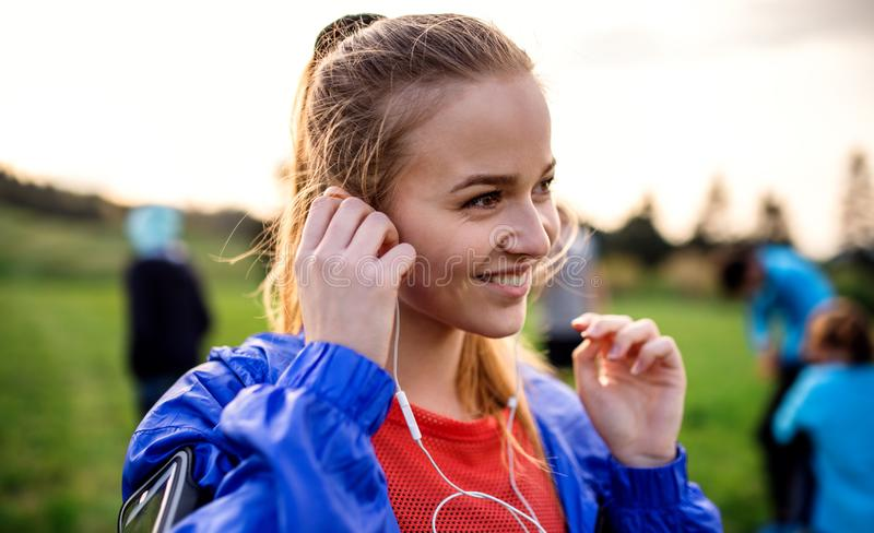 A portrait of young woman with earphones doing exercise in nature. A portrait of young women with earphones resting after doing exercise in nature stock image