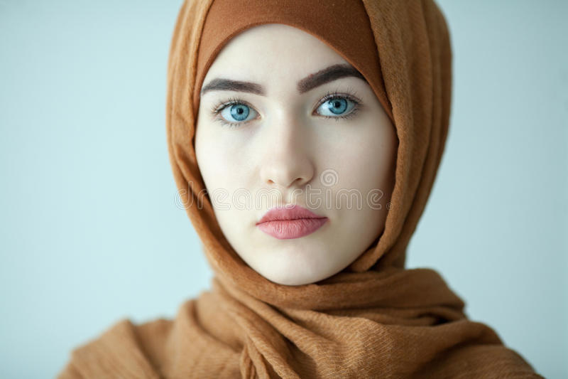 Portrait of a young woman eastern type in the modern Muslim clothes and beautiful headdress. Russia royalty free stock photography