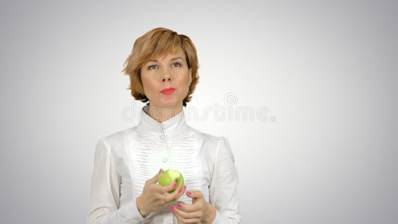 Portrait of young woman eating green apple on white background royalty free stock photography