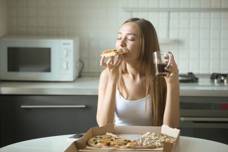 Portrait of a young woman eating pizza on the kitchen. Portrait of a young woman eating pizza, her eyes closed with pleasure, sitting at the kitchen table, drink stock photography