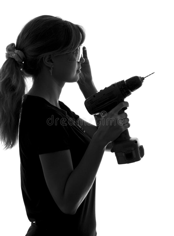Portrait of a young woman with an electric drill in his hands and protective clothing ready for operation stock photo