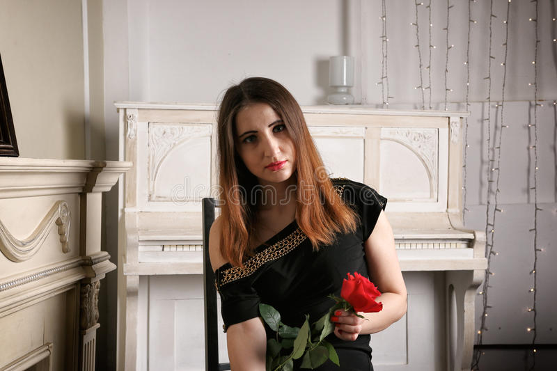 Portrait of young woman in evening dress with a red rose in his hands stock image
