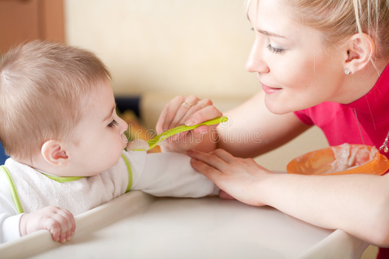 Download Portrait Of Young Woman Feeding Her Baby Stock Photo - Image: 8252550