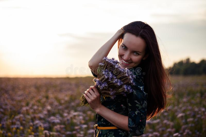 Portrait of a young woman in a flower meadow at sunset with a bouquet of purple flowers, smiling, copy space. Portrait of a young woman in flower meadow at royalty free stock photos