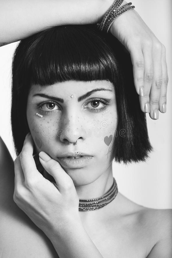 Portrait of young woman with freckles and heart-shaped stickers. Bobbed hair. Hands geometric position. Black and white stock image
