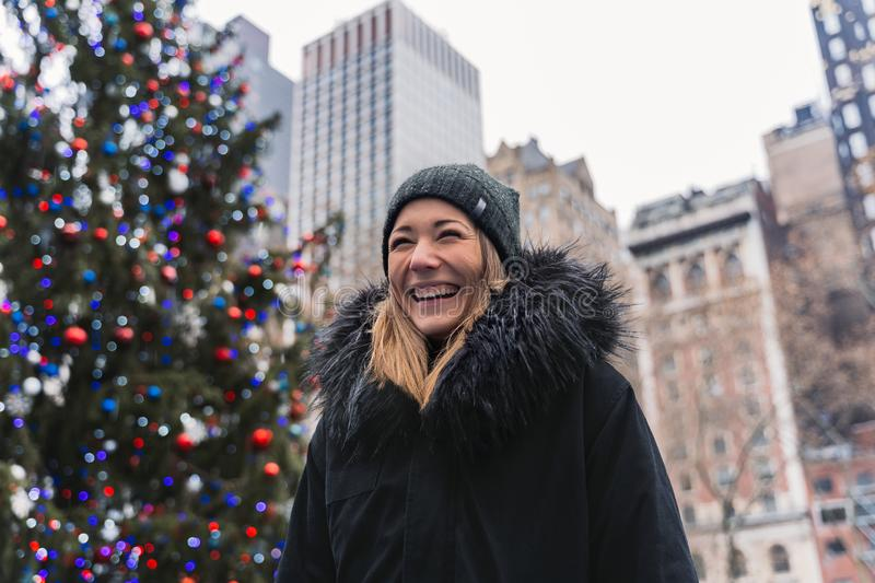 Portrait of a young woman in front of a christmas tree in the City of New York royalty free stock photography