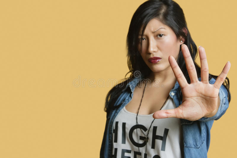 Download Portrait Of A Young Woman Gesturing Stop Sign Over Colored Background Stock Photo - Image: 29671734