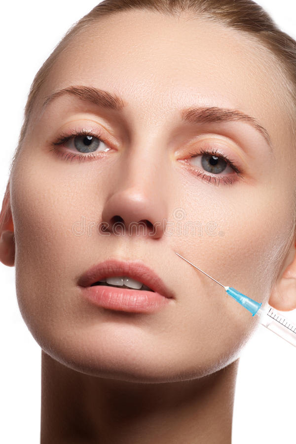 Portrait of young woman getting cosmetic injection. Beauty. Portrait of young woman getting cosmetic injection. Close-up of beautiful woman gets injection in her royalty free stock images