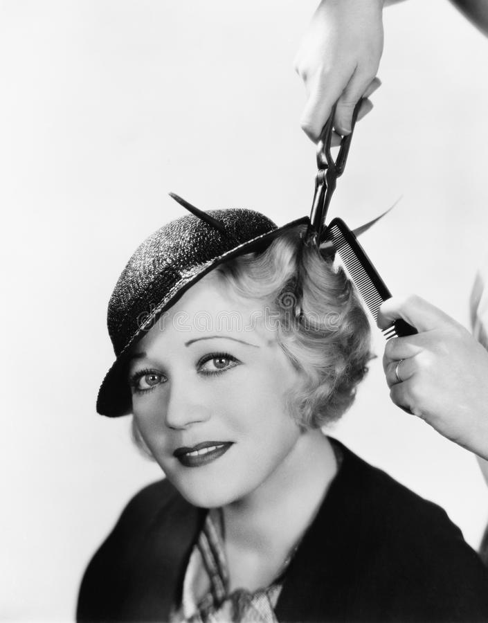 Portrait of a young woman getting her hair curled with an iron stock images
