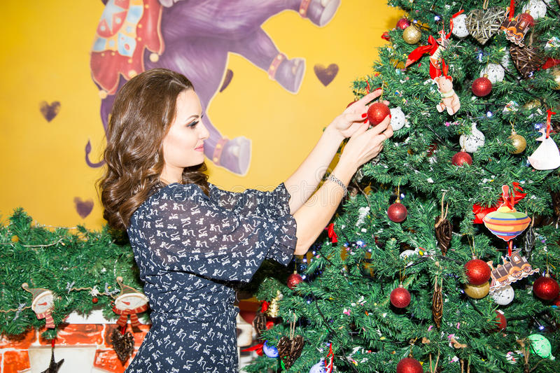Portrait of young woman with gift around a Christmas tree decorated. Girl on holiday new year royalty free stock photos