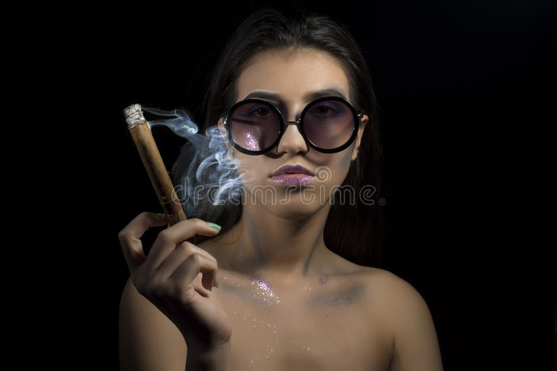 Portrait of a young woman. Portrait of a young girl with artistic make up and sunglasses smoking cigar stock images