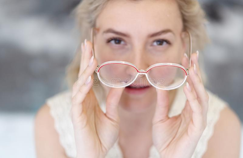 Portrait of a young woman with glasses and blond hair holding the glasses in front of her face, her face out of focus stock photo