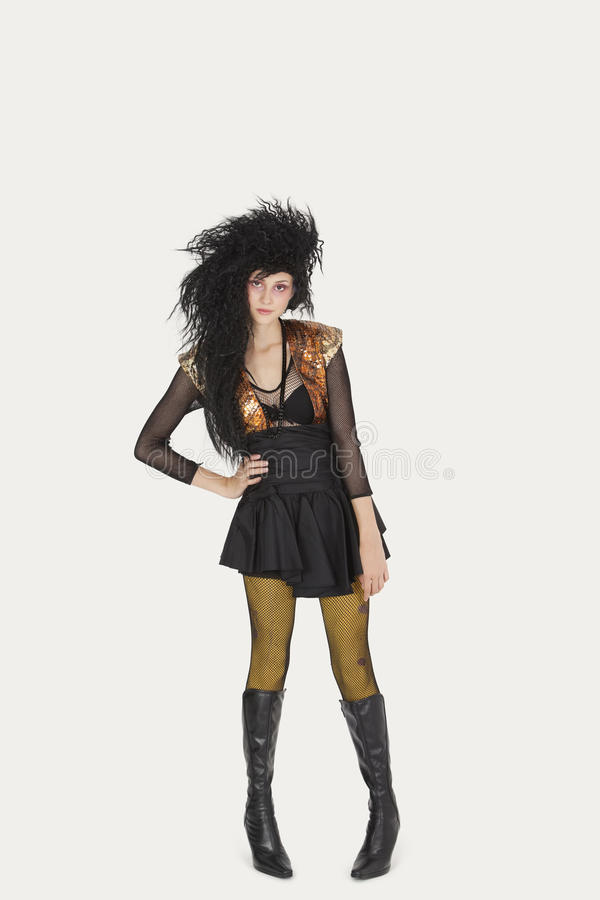 Portrait of young woman in gothic clothing over gray background royalty free stock photos