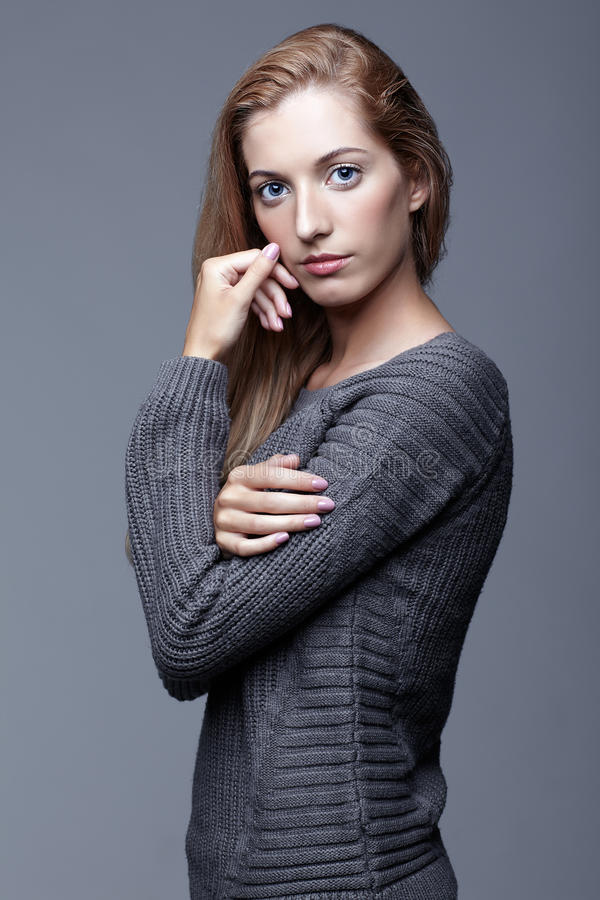 Portrait of young woman in gray woolen sweater. Beautiful girl p stock photos