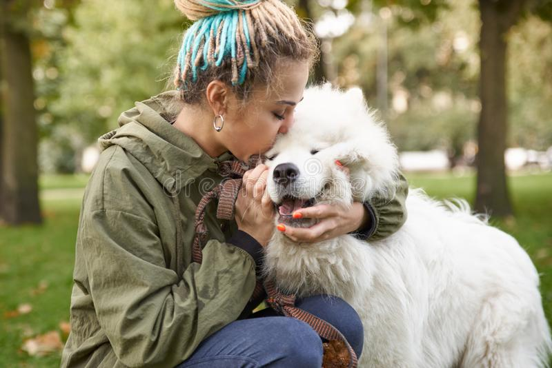 portrait of a young woman in a green coat and dreadlocks, kissing with his snow-white Samoyed dog in the autumn Park royalty free stock images