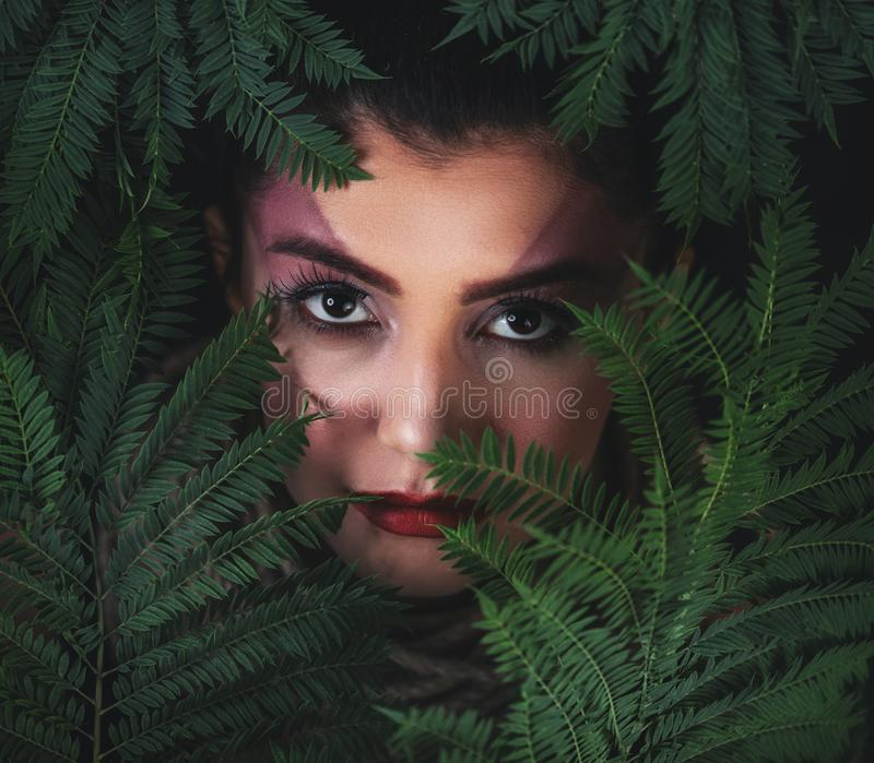 Portrait of young woman with green leaves background. Beauty concept. Portrait of young woman with green leaves background. Beauty concept stock photos