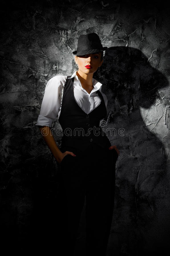 Portrait of young woman in hat on wall stock images