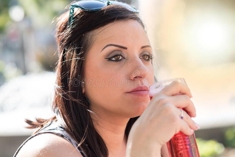 Portrait of a young woman having a drink outside, light effect. Portrait of a pretty young woman having a drink outside, light effect royalty free stock photography