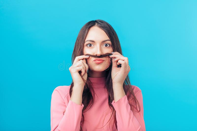 Portrait of young woman having fun shows moustache hair isolated on blue background stock photos