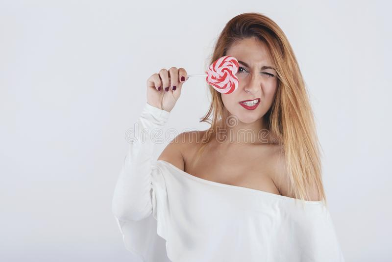 Portrait of young woman with heart shaped lollipop. On white background stock images