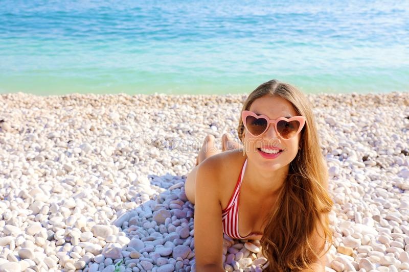Portrait of young woman with heart sunglasses lying on pebbles beach. Summer holidays concept.  royalty free stock photos