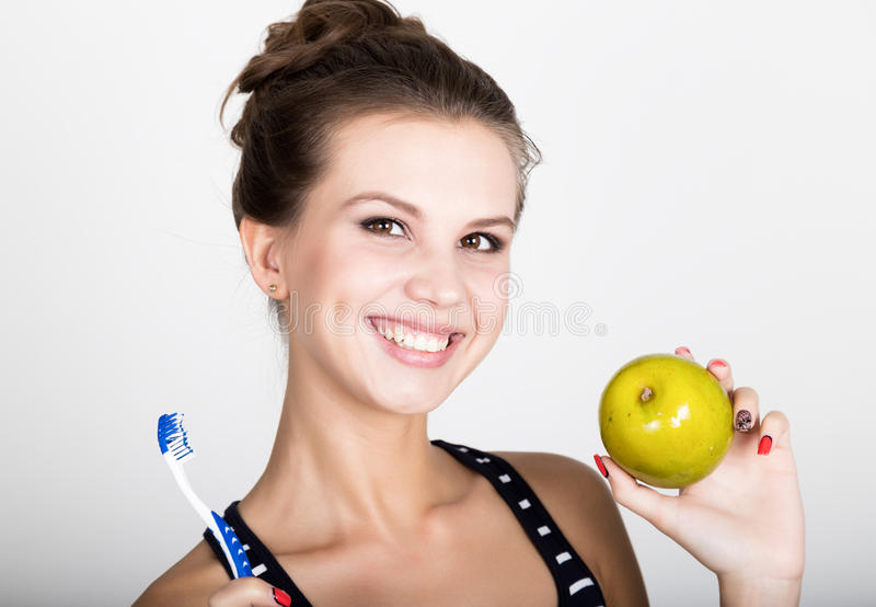 Portrait of young woman holding an apple and toothbrush, dental health concept stock image